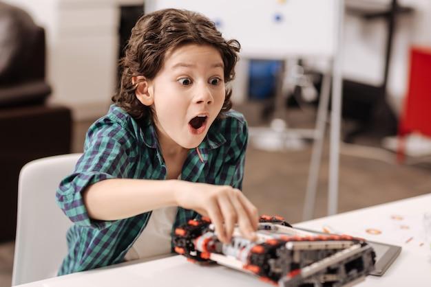Wyrażanie prawdziwego zdziwienia. zdziwiony słodki zabawny chłopiec siedzący w klasie i dotykający urządzenia podczas programowania robota
