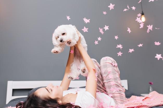 Wyrażanie prawdziwych pozytywnych emocji młodej radosnej kobiety w piżamie z kręconymi włosami brunetki bawiącej się z małym pieskiem w spadających różowych świecidełkach na łóżku