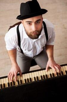 Wyrażanie siebie muzyką. widok z góry na przystojnych brodatych młodych mężczyzn grających na pianinie i patrzących na kamerę