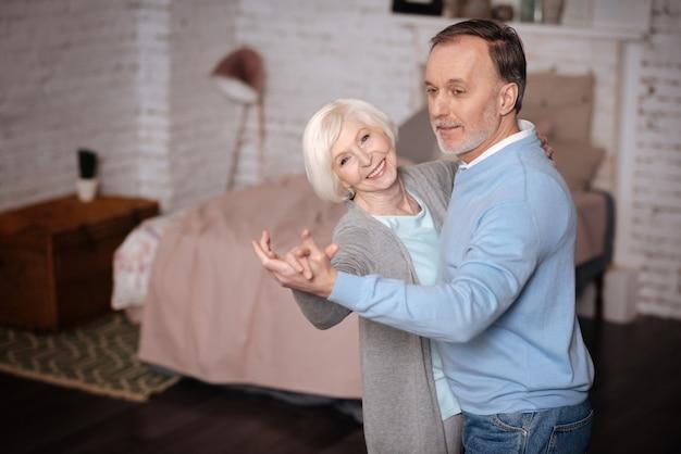 Wyrażanie szczęścia. uśmiechnięta starsza pani tańczy z kochającym mężem w domu.