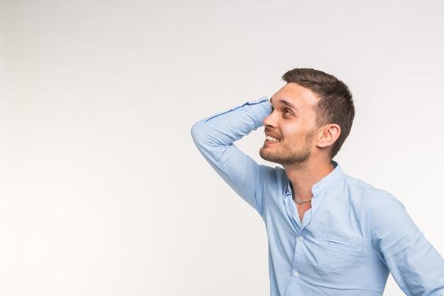 Wyrażenia i koncepcja osób - portret młodego mężczyzny brodaty trzymając się za ręce na głowie na białym tle nad białą ścianą.