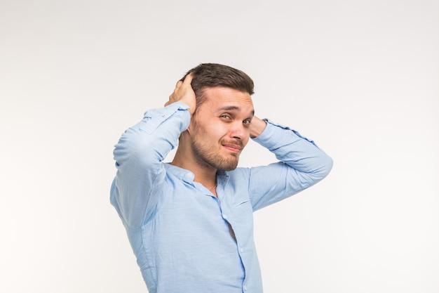 Wyrażenia i koncepcja osób - portret młodego mężczyzny brodaty, trzymając się za ręce na jego głowie na białym tle