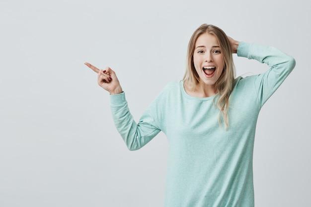 Wyrażenia ludzkiej twarzy, emocje i uczucia. zaskoczona zszokowana młoda blondynka w zwykłych ubraniach wskazująca palcem wskazującym pustą ścianę, zaskoczona cenami sprzedaży, z szeroko otwartymi ustami