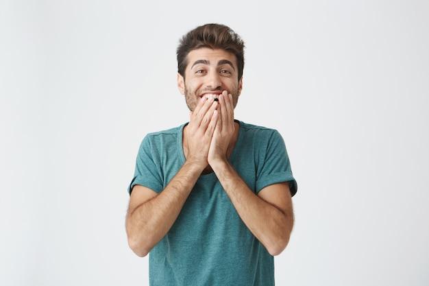 Wyrażenia ludzkiej twarzy, emocje i uczucia. zaskoczony i zdziwiony brodaty młody mężczyzna w niebieskiej koszulce wskazuje na pustą ścianę, mówiąc, że ma pomysł