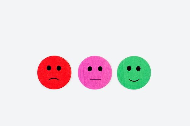 Wyrażenia twarzy wykonane za pomocą okrągłych kolorowych drewnianych guzików na szarym tle