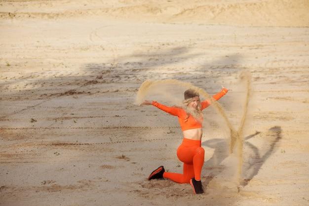 Wyrazista sportsmenka rzuca piaskiem, robiąc wypad na plaży.