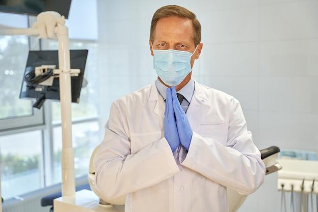 Wyrazisty dentysta wykonujący błagalny gest rękami