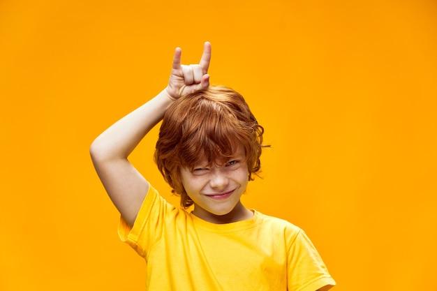 Wyrazisty rudowłosy chłopiec trzymający dwa palce nad głową rogów kozła
