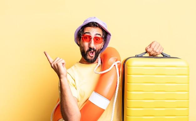 Wyrazisty szalony brodaty mężczyzna w kapeluszu i okularach przeciwsłonecznych z walizką. koncepcja wakacji