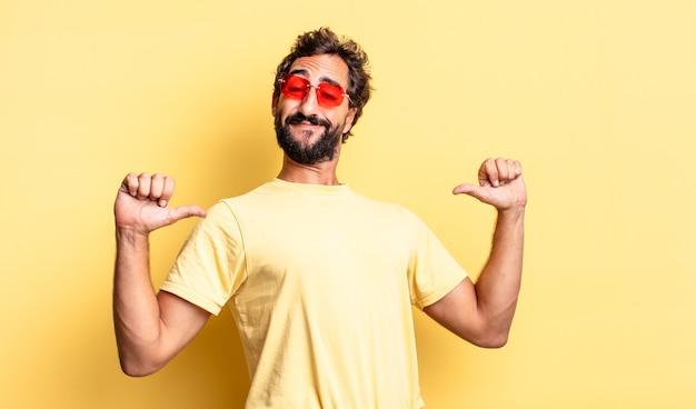 Wyrazisty szalony brodaty mężczyzna w okularach przeciwsłonecznych z kopią miejsca na żółtej ścianie