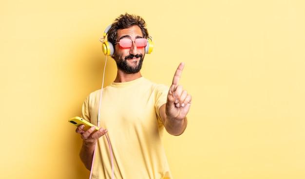 Wyrazisty szalony mężczyzna uśmiechający się dumnie i pewnie robiąc numer jeden ze słuchawkami