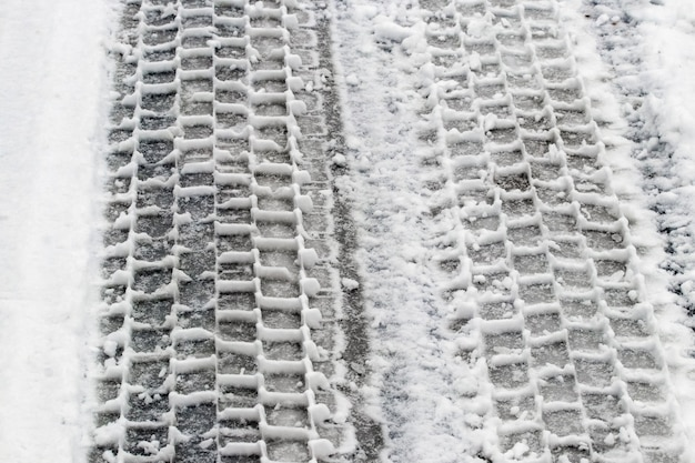 Wyraźne ślady opon samochodowych na śniegu podczas odwilży, śliskiej nawierzchni