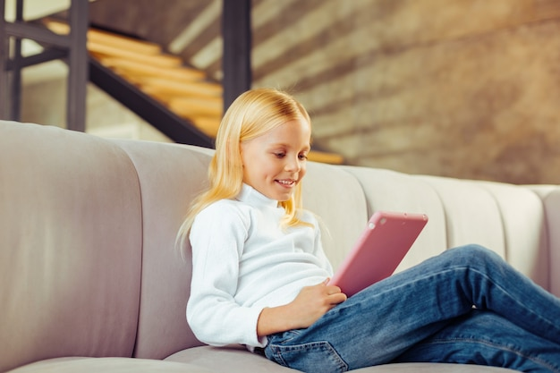 Wyrazy twarzy. radosny przedszkolak siedzący na kanapie podczas gry online