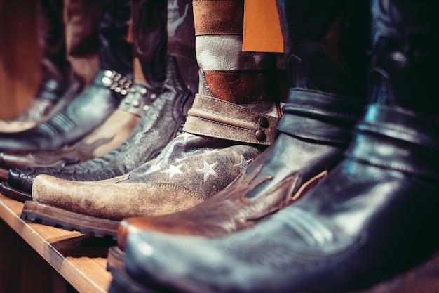 Wyrównane buty kowbojskie na półce w sklepie