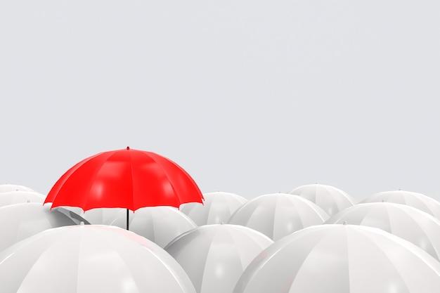 Wyróżniający się jeden czerwony parasol jest wyższy niż pozostałe na szarym tle.