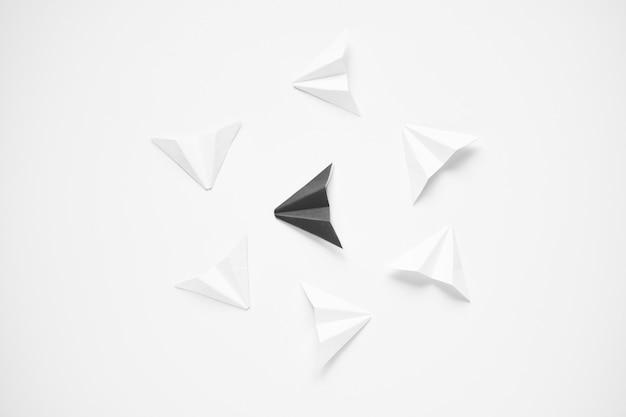 Wyróżnij się koncepcja. czarny papierowy samolot stoi out od linii biel