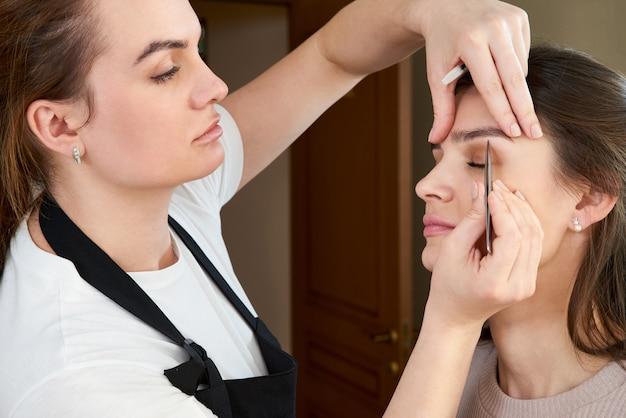 Wyrywanie kobiecych brwi pęsetą podczas korekcji brwi w gabinecie kosmetycznym