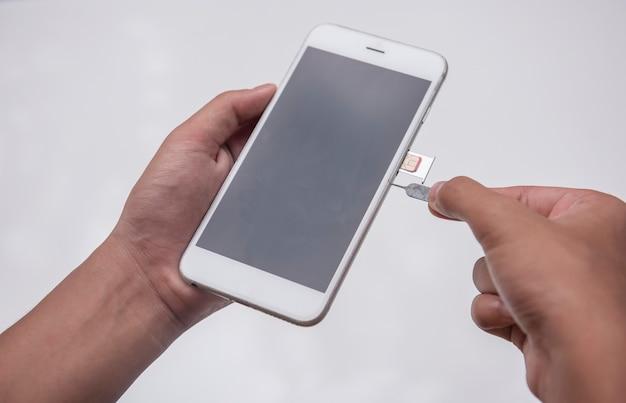 Wyrzutnik karty sim ręki człowieka z narzędziem do wyrzucania szpilek