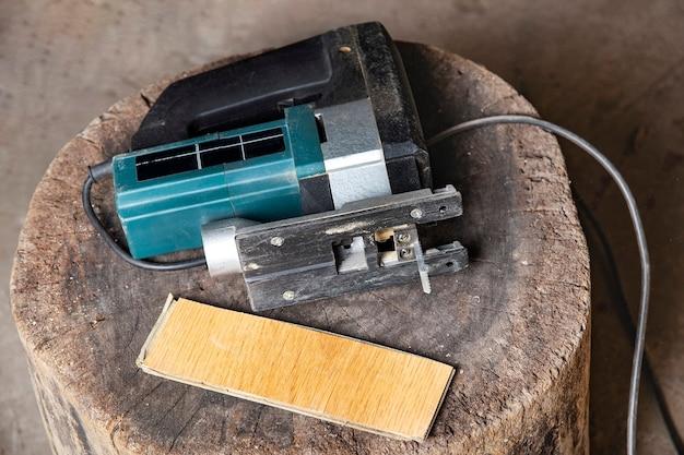 Wyrzynarka elektryczna z ostrą piłą i płytą laminowaną leży na drewnianym cięciu w warsztacie