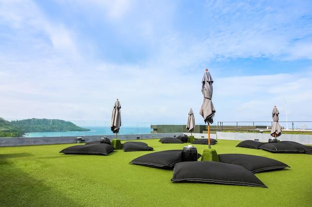 Wyściełane siedzisko z parasolem na zielonym polu