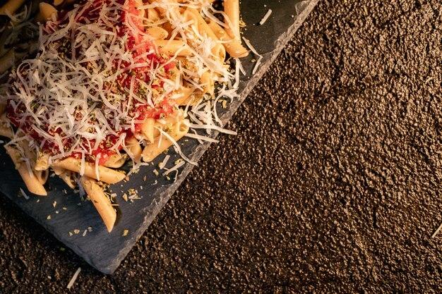 Wyśmienicie apetyczny klasyczny makaronowy makaron z sosem pomidorowym, parmezanem i świeżą bazylią, widok z góry