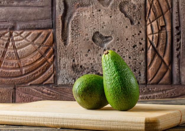 Wyśmienicie avocado w tnącej deski bocznym widoku na drewnianym