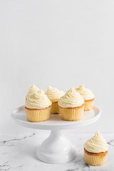 Wyśmienicie babeczki na torta stojaku nad marmuru stołem przeciw białemu tłu