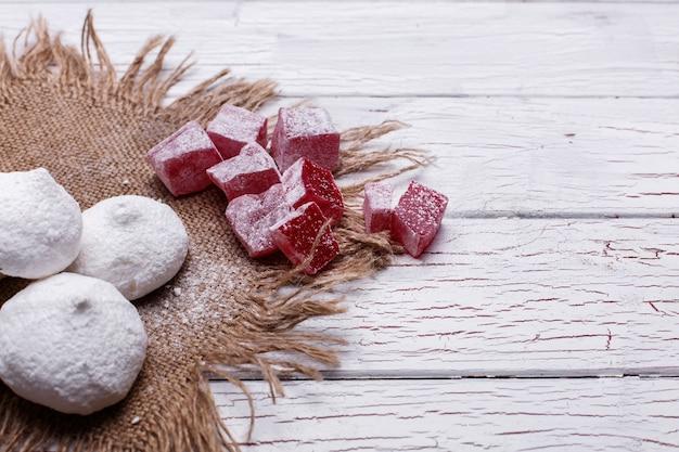 Wyśmienicie biali i czerwoni ciastka dla herbaty słuzyć na białym drewnianym stole