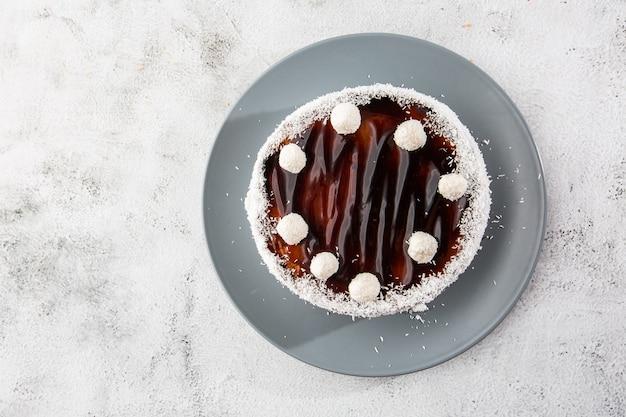 Wyśmienicie cały czekoladowy tort na talerzu z kokosowymi cukierkami na wierzchołku na stole na marmurowym tle. tapeta do cukierni lub menu kawiarni. poziomy.