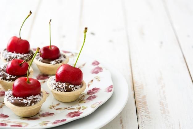 Wyśmienicie czekoladowy tarta z wiśnią i kokosem na białym drewnianym stole