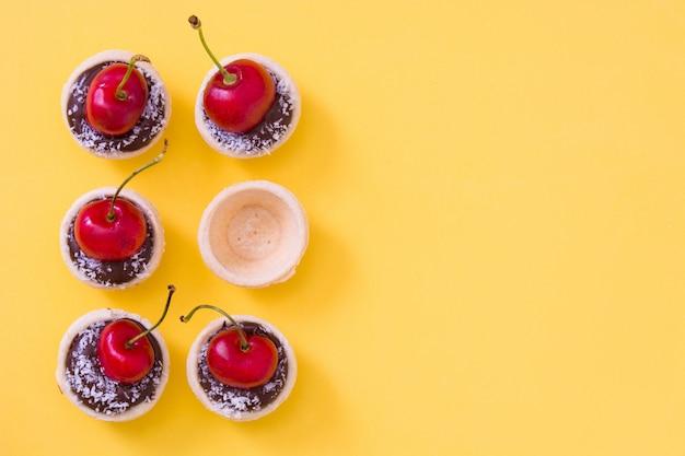 Wyśmienicie czekoladowy tartlet z wiśni i koksu wzorem na kolor żółty ściany kopii przestrzeni