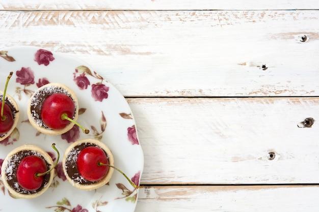 Wyśmienicie czekoladowy tartlet z wiśnią i koksem na białej drewnianej stół kopii przestrzeni