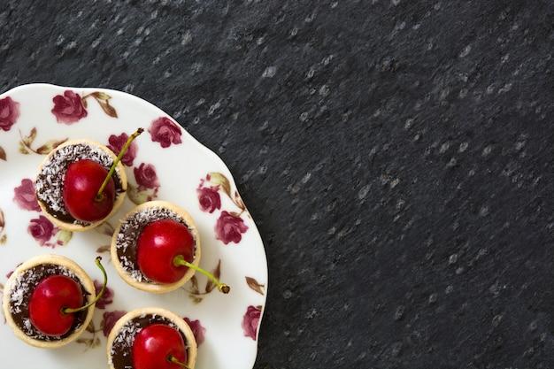 Wyśmienicie czekoladowy tartlet z wiśniowym i kokosowym wzorem na czerni ściany kopii przestrzeni
