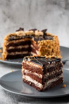 Wyśmienicie czekoladowy tort z białą kokosową śmietanką na talerzu na stole na marmurowym tle. tapeta do cukierni lub menu kawiarni. pionowy.