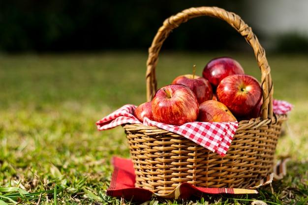 Wyśmienicie czerwoni jabłka w słomianym koszu