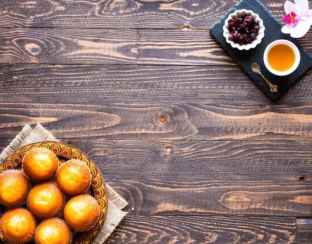 Wyśmienicie domowej roboty muffins z jogurtem, na drewnianym tle z przestrzenią dla teksta.