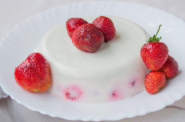 Wyśmienicie domowej roboty tortowy deserowy śmietanka z truskawkami na białym talerzu