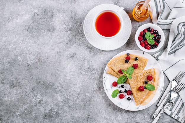 Wyśmienicie krepy śniadanie na szarość betonu stołu tle. naleśniki z jagodami