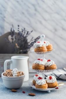 Wyśmienicie muffins na torta stojaku blisko pucharu płatki kukurydziane i migdał na betonowej powierzchni