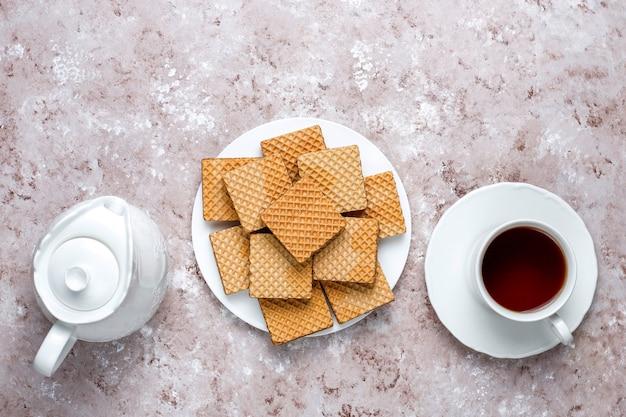 Wyśmienicie opłatki i filiżanka kawy dla śniadania na lekkim tle, odgórny widok