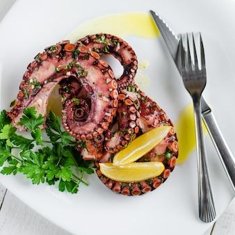 Wyśmienicie ośmiornicy sałatka z opatrunkiem, cytryną i pietruszką na białym tle. zdrowe odżywianie. gotowanie owoców morza