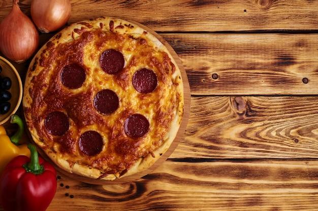 Wyśmienicie pizza z salami na drewnie. rustykalny. jedzenie.
