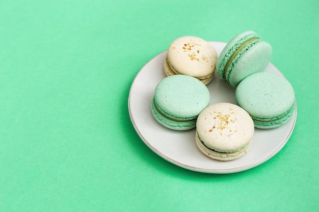 Wyśmienicie słodcy deserowi macaroons w bielu talerzu na mennicy tapetują tło