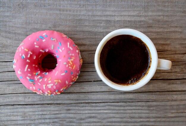 Wyśmienicie słodki świeży różowy pączek i filiżanka kawy na starym drewnianym tle śniadanie, fast food, piekarni pojęcie minimalizm, odgórny widok.