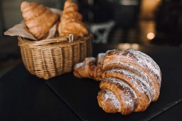 Wyśmienicie śniadanie z świeżymi croissants na czarnym tle, wyśmienicie wypiekowa odgórnego widoku kopii przestrzeń dla teksta