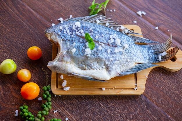 Wyśmienicie świeża ryba na ciemnym tle. ryba z aromatycznymi ziołami, dietą lub gotowaniem