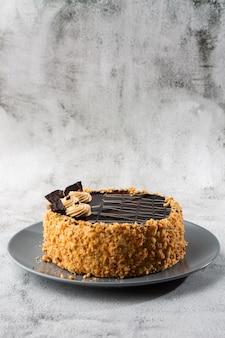 Wyśmienicie tort na talerzu na stole na marmurowym tle. tapeta do cukierni lub menu kawiarni. pionowy.