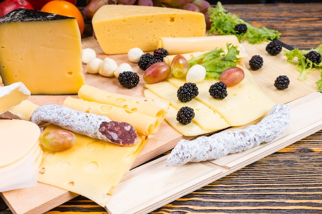 Wyśmienita deska serów dla smakoszy z rozmaitymi serami, wędliną kiełbasą i świeżymi owocami serwowana na rustykalnym drewnianym stole z słojami drewna