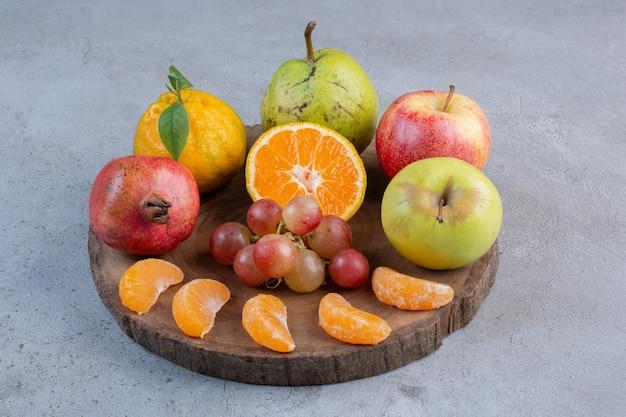 Wyśmienita porcja owoców na desce na marmurowym tle.