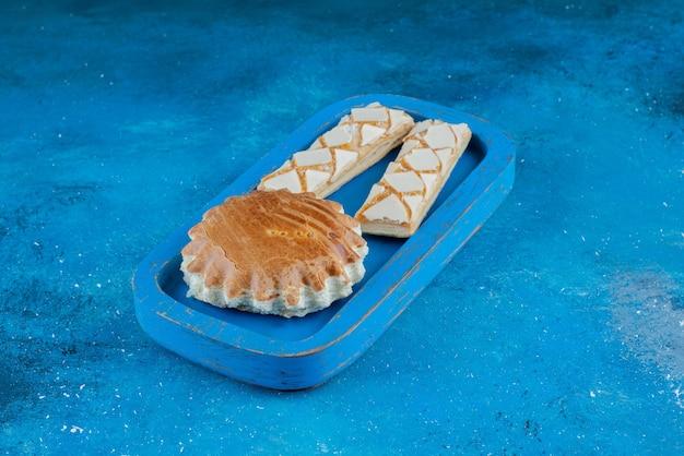 Wyśmienite ciastko na niebieskiej drewnianej tacy, na niebieskim tle. wysokiej jakości zdjęcie